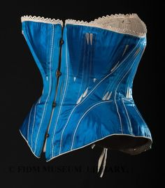 "Late 1860s. ""Corsets were shaped to place somewhat less pressure on the hips. The resulting silhouette, though hidden under layers of fabric, was a shapely hourglass. As seen in in our blue silk satin corset, godets at hip and bust allowed for a relatively roomy fit."""
