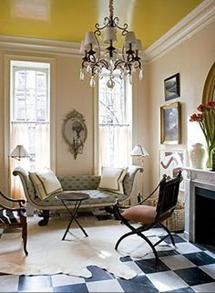 Glossy Yellow Painted Ceiling, checkered floor, chandelier, vintage couch, mirrors, fireplace = love.
