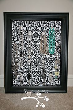 pinboard covered in fabric with clear knobs screwed in the holes.  So pretty and easily customizable.