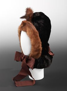 Bonnet 1870, American, Made of silk and fur~~~~~High-style verticality and luxurious material are blended with witty detailing in this fetching winter bonnet. The whimsical mink head ornament with upright tails evokes the playful and impish charm of the mischievous animal.
