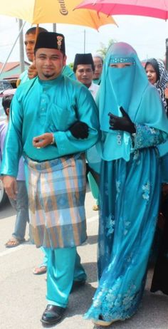 Pretty blue niqabi; And they match! I don't know where this is. From man's attire, not Arab. Pakistan, India, Malaysia?? Anybody know??
