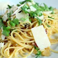Porties: 8  1 pakje (500 gr) spaghetti 1 el olijfolie 200 gr spekblokjes of pancetta 1 el olijfolie 1 fijngehakte ui 1 geperst teentje knoflook 4 el droge witte wijn (optioneel) 4 losgekopte eieren 50 gr geraspte Parmezaanse kaas zout en versgemalen zwarte peper naar smaak handvol fijngehakte verse peterselie geraspte Parmezaanse kaas (om over het gerecht te strooien)