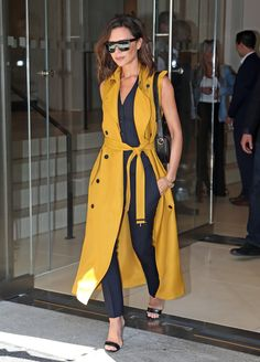 Victoria Beckham in a cumin-colored sleeveless trench, pin-striped suit and simple strappy sandals.