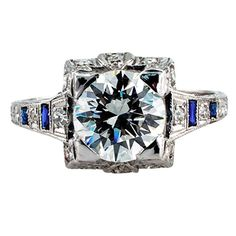 Art Deco Diamond Engagement Ring. 1.50 Carats G VS1 Art Deco Engagement Ring This authentic Art Deco engagement ring set with a fine transitional cut diamond weighing 1.50 carats, graded G color and VS1 clarity by EGL U.S.A., between shoulders set with alternating smaller diamonds and simulated French-cut blue sapphires, to the gallery decorated with additional diamonds, openwork and crisp engraving to the tapering shank. Made in platinum, c 1925