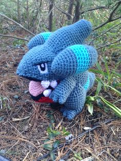 Pokemon Inspired: Gible Amigurumi Crochet Plushie/Plush Toy  Handmade plushie (in crochet Amigurumi style) of the ever adorable dragon Pokemon, Gible, from the Sinnoh Region!   Gible measures roughly 9in tall, 8in wide and 9in long. He is completely crocheted detail all but for his eyes which are needle-felted on. All of his details were done from his tongue and teeth, his open mouth and fin/horns.   Gible can stand on his own due to the balance of his feet and tail.   Gible is currently…