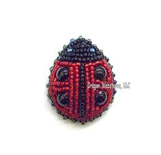 "Beaded Ladybug Pin • This awesome ladybug pin is fashioned from tiny beads. The little glass beads are sewn onto a black velvet backing and different colors of beads are used to create the head, eyes and wing cases on the ladybug. The spot are 4 large black beads. The pin has a traditional style clasp. Size: About 1-1/2"" long"