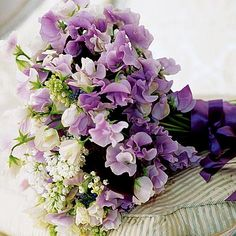 bridal bouquet of white lilacs, lily of the valley, sweet peas and muscari.