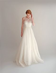 This sweet and delicate wedding gown combines an ivory lace illusion bodice with a full silk organza skirt. The bodice is fully-boned for structure and