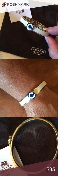 Coach Hinged Bangle Bracelet This is a Coach Bangle bracelet. Bone enamel over gold. The top clasp with the Coach Opt-Art C is Navy. The hinge clasp is on top to prevent bumping and unlocking. Oval in shape to keep its position. Excellent condition. Comes with flannel bag and care card. Coach Jewelry Bracelets