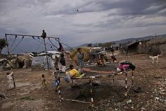 April 1, 2013. Pakistani children, who were displaced with their families by 2010 floods from Pakistans Sindh province, play on a trampoline without paying, after the owner of the trampoline left the place due to a heavy rainfall, in a slum on the outskirts of Islamabad. Muhammed Muheisen—AP