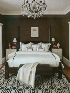 bedrooms - white brown wood poster bed white brown geometric rug white nightstands bronze crystal chandelier white bedding brown stitching brown leather bench beige cashmere throw blanket brass sconces chocolate brown walls