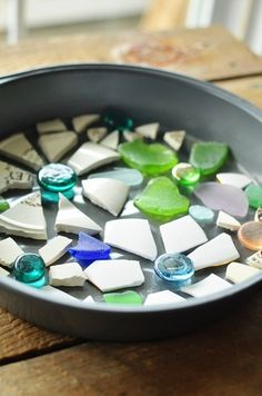 How to Make Stepping Stones  with a Cake Pan: Arrange mosaic items design side down on contact paper. Pour vaseline around cake pan - pour cement into cake pan in 2 layers, with a square of chicken wire in between. Set for 2 days