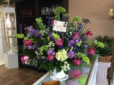 Purple roses, mini green hydrangeas & bells of Ireland funeral arrangement by Donna Jeffries