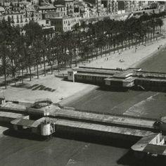 """Fotografía aérea del Postiguet en el año 1956. En primer plano, los dos últimos balnearios en uso: """"La Alianza"""" y """"La Alhambra"""". Extraída de """"Alicante en Blanco y Negro""""-Sonia Castedo"""