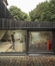 Paris studio Marchi Architectes layered up timber slats of different thicknesses and proportions to give an irregular texture to the walls of this sunken house extension in Normandy, France