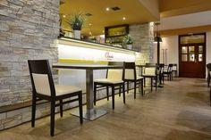 Dřevěné židle a lavice v interiéru hotelu Classic 1