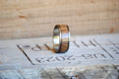This ring is a Stainless Steel Band with a channel filled with Walnut Wood Inlay.  Please send us a message with your desired Ring Size.  We love to hear your ideas. Please message us with custom ring ideas, or if you want anything special included/changed in this ring. Remember that we do different metals for the inner band. This ring can come with either STAINLESS STEEL, SILVER, YELLOW GOLD, WHITE GOLD, or ROSE GOLD  We make all our rings from handcrafted materials, and they are made…