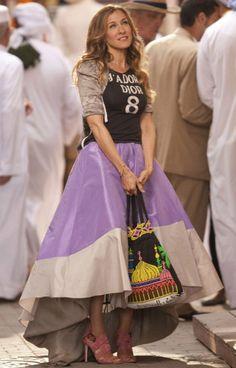 Au cours d'une escapade avec ses meilleures amies, Carrie croise Aidan en plein cœur du souk marocain, vêtue d'un t-shirt à numéro Dior et d'une jupe longue bicolore, accompagnés d'une paire de sandales cloutées et d'un sac cabas ethnique.