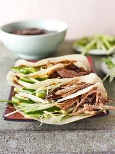 cut some fat off the duck and sit it on a rack on a roasting tin and put it in the oven for hours on end. Then, I take it out, set to with some forks and put some shop-bought Chinese pancakes on to steam. I chop and slice cucumber and spring onions and open a jar of Hoisin sauce