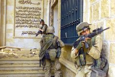 US Marines Corps (USMC) Marines from the 1st Battalion, 7th Marines (1/7), Charlie Company, Twentynine Palms, California (CA), cover each other with 5.56 mm M16A2 assault rifles as they prepare to enter one of Saddam Husseins palaces in Baghdad as they takeover the complex during Operation Iraqi Freedom. 9 April 2003