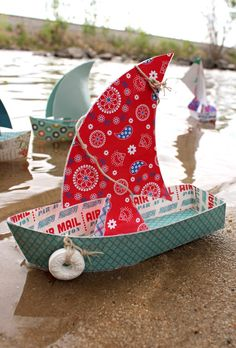 Floating Boat Paper Toy: easy to make and fun for kids! Cut paper into the shape of a boat, laminate, put it together, and hot glue the seams to prevent leaks.