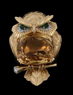 A gem set owl brooch by Cartier, circa 1960, with a mixed cut citrine set body, and emerald and diamond accented eyes, with engraved feather decoration, sitting on a diamond accented branch, signed Cartier London.