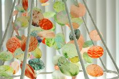 Wax paper + Crayons + lampshade = rainbow chandelier.  I'm thinking of combining this with the faux capiz shell chandelier I pinned earlier to cover the hideous light fixture in my kitchen.