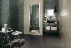 This modern bathroom is tiled in large, beige tiles on the right, and dark subway tiles to the left and behind the shower enclosure. Glass tiles cover the vanity with a simple vessel sink. Urban Bathroom, Bathroom Windows, Wall Tiles Design, Luxury Master Bathrooms, Modern Bathroom, Bathroom, Bathroom Doors, Luxury Bathroom, Tile Bathroom