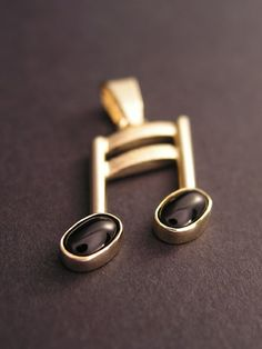 Golden music note in form of pendant. Gold with black onyx stone.