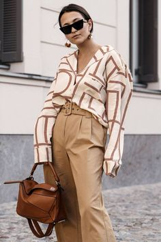 Tan high waist pants with belt, geometric print shirt, with tan handbag. Neutral street style fall outfit.