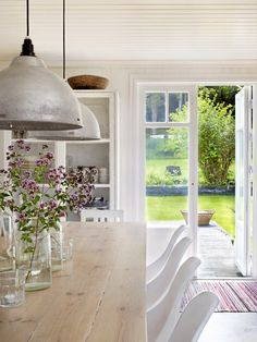 Love the mix of country style kitchen with edgy industrial style lighting at low level over the dining table