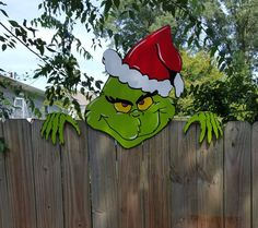 the grinch is coming over the christmas fence climber by hashtagartz on etsy christmas crafts