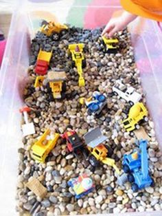 crate of rocks with lil dump trucks and cars for inside play