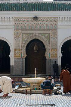 Muslim men performing wudu in front of masjid