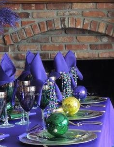 Elegant Mardi Gras Table Centerpieces | Each place setting starts with a gold charger which is topped with a ...