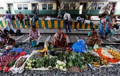 Kolkata, India  Street sellers sit between railway tracks waiting for customers to arrive on passing trains