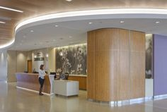 The first-floor reception area incorporates more white curvilinear forms with natural design elements in neutral, calming colors and translucent surfaces. Photography of details within the Texas prairie landscape provide patients with a welcoming environment upon arrival. Photo: © Brad Feinknopf 2015