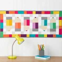 """Cute colored pencils stack up in this fast and fun little quilt that is a perfect project for scraps.  Pencil points are quick to piece together with a twist on flying geese.  The finished size is about 42-1/2"""" x 18-1/2"""".Compatible with these fabric cutters:GO!GO! Big      Studio**Must use with GO! Die AdapterLearn How to download quilt patterns.Fabric provided by Cloud 9 Fabrics"""