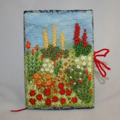 I ❤ embroidery . . . Cottage Garden Notebook- Sky blue wool fibers have been felted to a background of kunin felt (from recycled plastic bottles). Textured, hand-dyed wool tops, some of them with lovely curls, have been felted in clumps to represent the planting. Stitching in fine cotton has been added to the sky to 'stabilise' the felting. Simple embroidery stitches, cotton threads, crewel, tapestry & knitting wools, have been used to create more foliage & the pretty flowers.