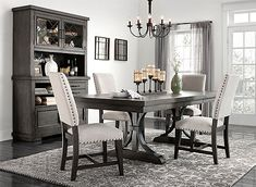 When it comes to the Halloway 5-piece dining set, strong lines and eye-catching detail create a transitional look that serves up fine dining for a variety of decorating styles. Distressed, espresso finish and parquet pattern oak veneers showcase this set's natural beauty, while details like nailhead trim add a rustic touch. The upholstered chairs feature neutral colored fabric and are sure to make the sit-down dinner a comfortable experience.