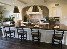 White galley style kitchen with elaborate custom white stove head.  Long rectangular white kitchen island with dark top comfortable accommod...