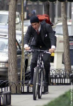 Leaving his mother's Fifth Avenue apartment on his bicycle in NYC.