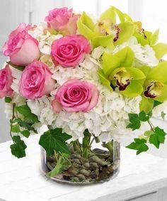 Rosen, grüne Orchideen und weiße Hortensien in einer Glasvase