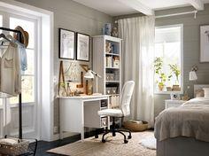 Roh v ložnici s bílým stolem, knihovnou a otočnou židlí.