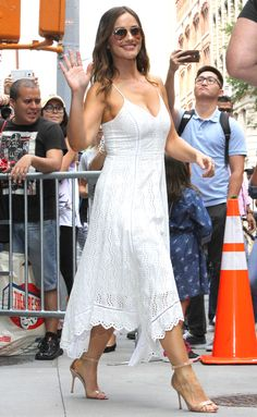 MINKA KELLY wearing a flirty, V-neck white sundress with a whimsical handkerchief hem and some nude sandals,