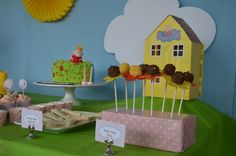Peppa Pig house from my daughter's toy box atop an upside down bowl (sticky taped to the table) then green table cloth over the top. Hand cut Cloud and store bought Yellow Sun hanging against blue single flat sheet, as sky. Pedro Pony Pops, Marshmallows on sticks, dipped in white chocolate and then sprinkles with coloured paper flower petals pushed up sticks