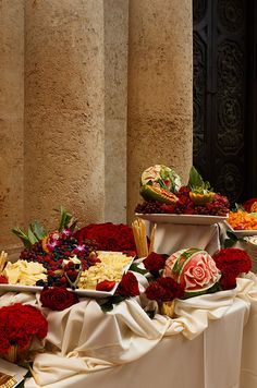 A fruit and cheese buffet decorated with red roses and carved melons.