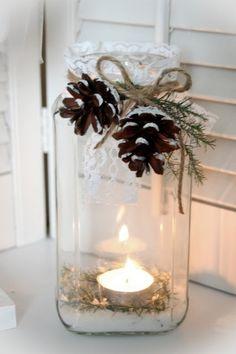 une bougie blanche en pot en verre décoré de pommes de pin et ficelle