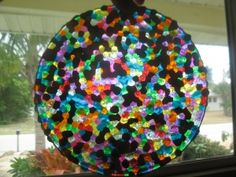 """Homemade suncatcher! So simple! Layer cheap plastic beads in cake pans (no lining required), melt at 400 for 20 minutes,let cool, & then just flip them out. Drill a hole in it to make it a suncatcher! Great """"craft"""" for kids (choose the colors, arrange them in the pans) to make as gifts for grandparents or teachers. Oooh - could small ones be used as coasters? Look like glass but not breakable!"""