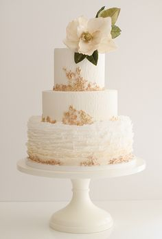 Three-Tiered White Cake with Gold Details. This romantic, creamy ivory confection by cake artist Maggie Austin is perfect for Southern brides: The bottom tier is covered in her signature frills, while the top tiers are decorated with intricate bas-relief molding done in soft gold. Topping it off: a luscious sugar magnolia, flecked in gold.